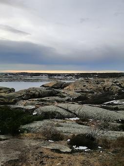 Pionowe zdjęcie skał otoczonych morzem podczas zachodu słońca w rakke w norwegii