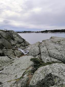 Pionowe zdjęcie skał otoczonych rzeką pod zachmurzonym niebem w norwegii