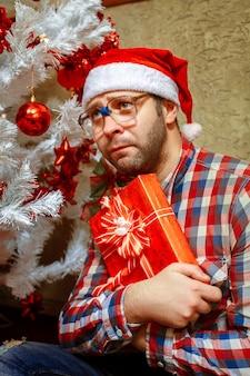 Pionowe zdjęcie smutnego samotnego mężczyzny z prezentem świątecznym