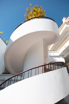 Pionowe zdjęcie spiralnych schodów budynku oświetlonego światłem słonecznym w huatulco w meksyku