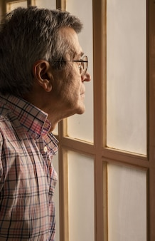 Pionowe zdjęcie starego mężczyzny w okularach patrząc przez okno