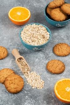 Pionowe zdjęcie stosu ciasteczek i płatków owsianych w misce i pokrojone na pół pomarańcze na szarej powierzchni.