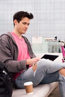 Pionowe zdjęcie studenta siedzącego na zewnątrz za pomocą tabletu obok koncepcji technologii roweru