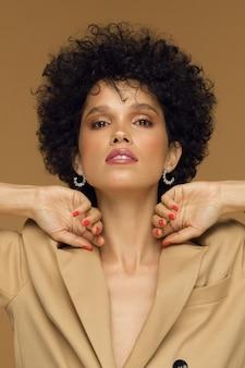 Pionowe zdjęcie studio, kręcona brunetka dziewczyna w modnej kurtce na beżowym tle. wysokiej jakości zdjęcie