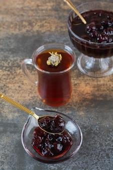 Pionowe zdjęcie świeżego dżemu domowej roboty z filiżanką herbaty