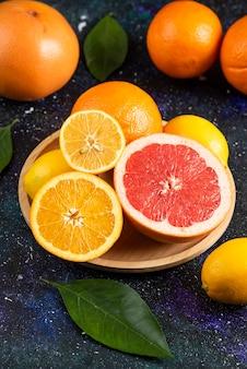 Pionowe zdjęcie świeżych owoców cytrusowych na drewnianym talerzu.