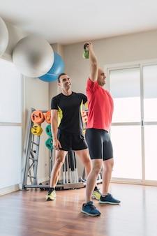 Pionowe zdjęcie trenera personalnego obok mężczyzny ćwiczącego z kettlebell na siłowni