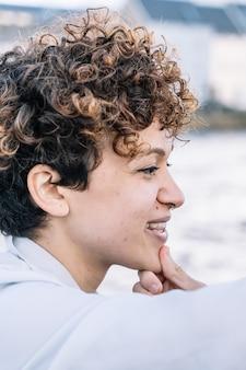 Pionowe zdjęcie twarzy młodej dziewczyny z kręconymi włosami podczas głaskania jej brody