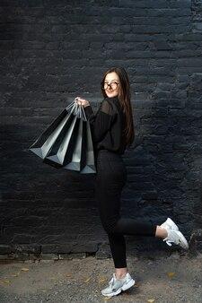 Pionowe zdjęcie w pełnym rozmiarze, młoda kobieta w formalnym stroju z czarnymi torbami na zakupy.