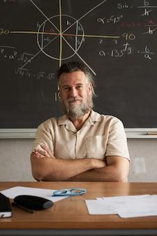 Pionowe zdjęcie wesoły nauczyciel patrzy w kamerę z rękami skrzyżowanymi na lekcji matematyki