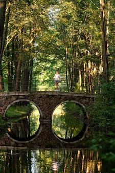 Pionowe zdjęcie z dużej odległości dziewczyny na kamienny most nad małą rzeką w parku