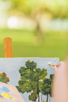 Pionowe zdjęcie z selektywnym naciskiem na kobiece malowanie dłoni pędzlem na płótnie
