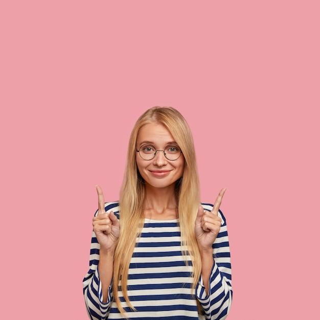 Pionowe zdjęcie zadowolonej pięknej blondynki nastolatki pokazuje kierunek do czegoś w górę, wskazuje oboma palcami wskazującymi do góry