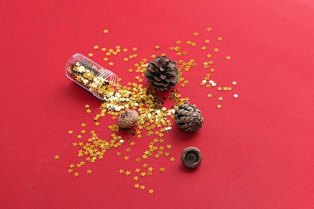 Pionowe zdjęcie złotej gwiazdy świecidełka na czerwonym tle. widok z góry. boże narodzenie tło. wysokiej jakości zdjęcie