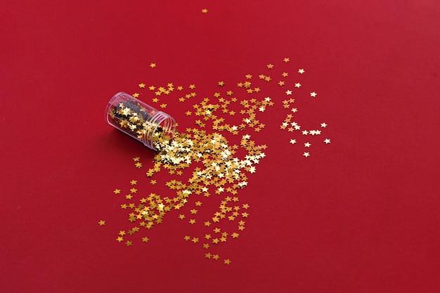 Pionowe zdjęcie złotej gwiazdy świecidełka na czerwonym tle. widok z góry. boże narodzenie tło