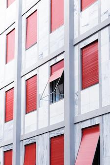Pionowo biały budynek z oknami z czerwonymi żaluzjami