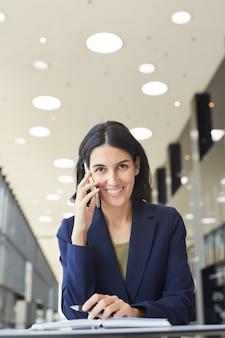 Pionowo do talii portret bliskowschodniego businesswoman rozmawiając przez telefon i stojąc przy stole na lotnisku lub w biurowcu