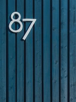 Pionowo drewniana niebieska ściana z pionowo ułożonymi laskami i białą liczbą osiemdziesiąt siedem