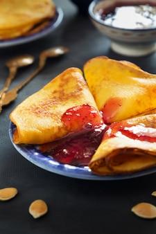 Pionowo fotografia bania ciency bliny z jagodowym dżemem na błękita talerzu