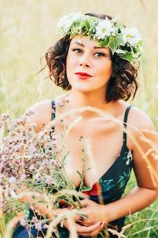 Pionowo Kaukaskiej Kobiety Z Wieńcem Z Kwiatami Zbierającymi Kwiaty Na Polu Darmowe Zdjęcia