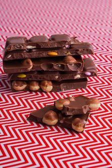 Pionowo pokrojone kawałki tabliczki czekolady z orzechami laskowymi i owocami. czerwone i białe tło.