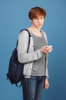 Pionowo portret przystojny młody rudzielec uczeń w przypadkowym stroju z plecaka mienia smartphone w ręce, z smutnym i niepewnym wyrażeniem.