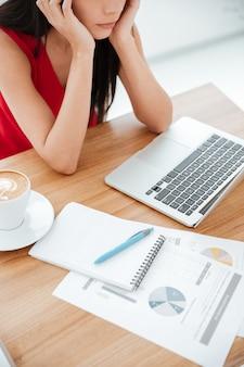 Pionowo przycięte zdjęcie zamyślonej kobiety w czerwonej koszuli siedzącej przy stole z laptopem i dokumentami w biurze