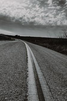 Pionowo strzał w skali szarości drogi wsi