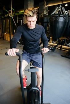 Pionowo wizerunek atletyczny mężczyzna używa przędzalnianego bicykl