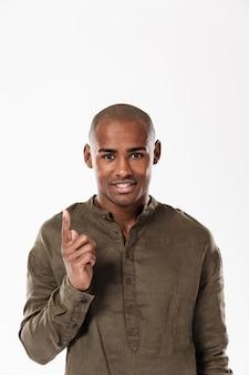 Pionowo wizerunek uśmiechnięty afrykański mężczyzna wskazuje w górę i patrzeje