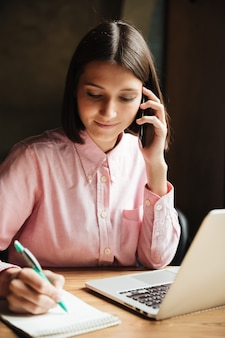 Pionowo wizerunek uśmiechnięty brunetki kobiety obsiadanie stołem