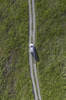 Pionowo wysoki kąt strzelał biały samochód jedzie ścieżką w zielonej dolinie