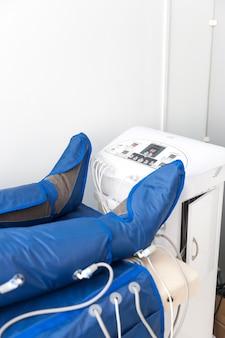 Pionowy baner z miejscem na kopię z nogami kobiety w specjalnej okładce w salonie piękności. alternatywne leczenie ciała. pressoterapia przeciwtłuszczowa.
