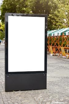 Pionowy billboard uliczny z białą przestrzenią kopii