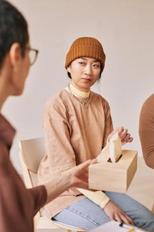 Pionowy, ciepły, stonowany portret młodej kobiety trzymającej pudełko tkanek podczas sesji terapeutycznej w grupie wsparcia