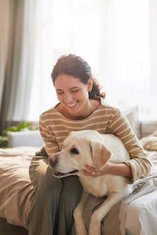 Pionowy ciepły stonowany portret uśmiechniętej młodej kobiety przytulającej psa leżącego na łóżku w przytulnym wnętrzu domu oświetlonym światłem słonecznym