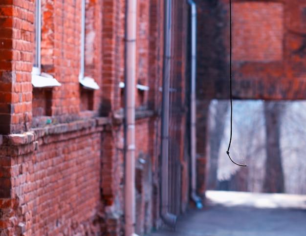 Pionowy drut na czerwonym tle ceglanego podwórka
