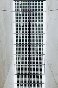 Pionowy niski kąt strzału metalowego sufitu w białym betonowym korytarzu