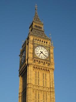 Pionowy niski kąt strzału z big ben w londynie pod błękitnym niebem