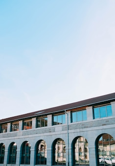 Pionowy niski kąt ujęcia betonowego budynku z odblaskowymi oknami pod czystym niebem