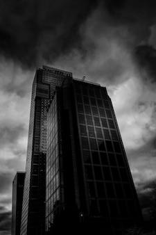 Pionowy niski kąt ujęcia w skali szarości z wieżowca z lustrzanymi oknami pod zapierającymi dech w piersiach chmurami burzowymi