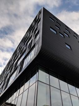 Pionowy niski kąt ujęcia wysokiego czarnego budynku ze szklanymi oknami