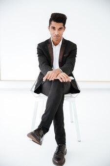 Pionowy obraz afrykańskiego biznesu człowiek w czarnym garniturze siedzi na krześle w biurze. obraz pełnej długości