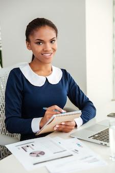 Pionowy obraz afrykańskiej kobiety biznesu w sukience z notebookiem i laptopem w miejscu pracy, patrząc na kamerę