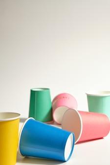 Pionowy obraz grupy kolorowych kartonowych kubków losowo umieszczonych na szarym tle