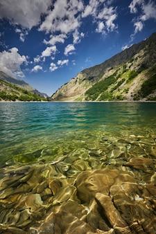 Pionowy obraz morza otoczonego skałami pokrytymi zielenią w słońcu
