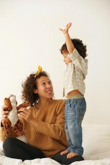 Pionowy obraz skoncentrowanego na sobie małego dwuletniego chłopca, który domaga się od swojej pięknej młodej matki, aby dała mu pluszową zabawkę. mama rasy mieszanej siedzi na białym łóżku i bawi się z synem