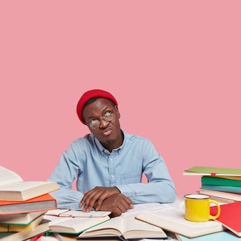 Pionowy obraz smutnego, zamyślonego afroamerykanina ubranego w stylowe ubranie, skierowanego ku górze, w okularach