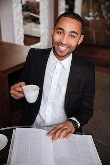 Pionowy obraz szczęśliwego afrykańskiego mężczyzny w garniturze siedzącego przy stole z dziennikiem, pijącego kawę w hotelu