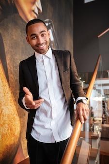 Pionowy obraz szczęśliwego afrykańskiego mężczyzny w garniturze stojącego na schodach i wskazującego